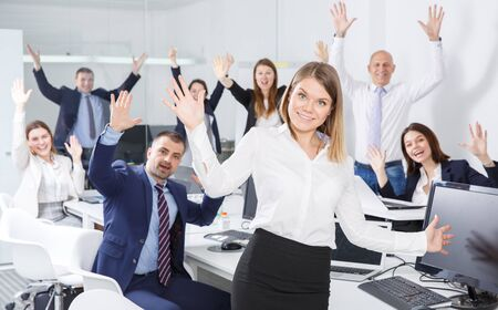 Portrait of happy successful business group with positive woman foreground in office