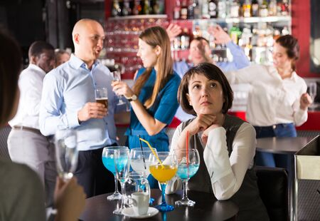 Sad woman sitting alone at office party in nightclub in background with cheerful workmates Stock fotó