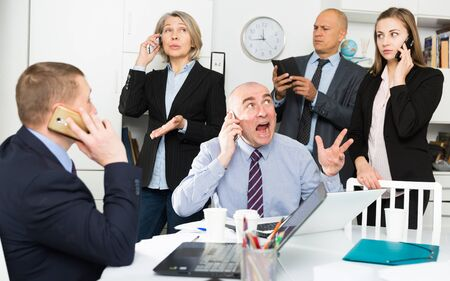 Crisis in the modern office: managers are urgent negotiations by phones Stockfoto