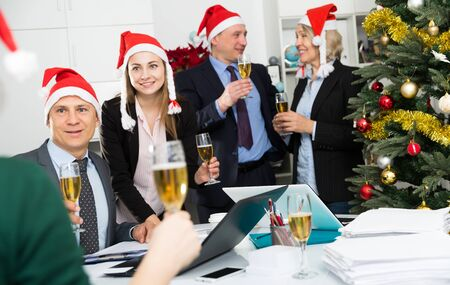 Group of happy colleagues in santa hats celebrating Christmas in office 版權商用圖片 - 129775695