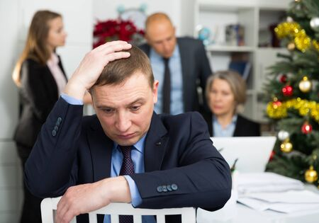 Upset businessman sitting in office with working colleagues behind 写真素材 - 129775705