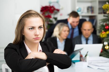 Irritated business woman sitting in office with working colleagues behind 写真素材 - 129775706