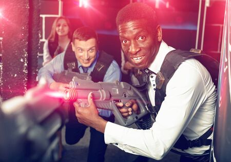 Positive smiling men and women in business suits playing laser tag emotionally in dark room