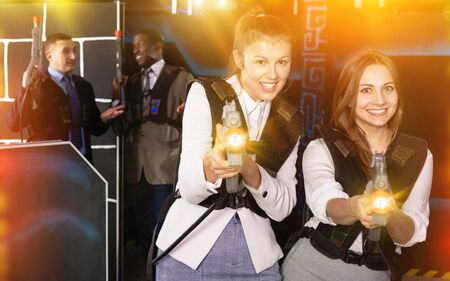 Portrait of two smiling  positive women in business suits playing laser tag with co-workers 写真素材