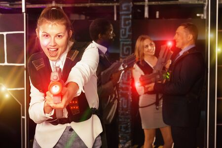 Emotional portrait of female playing laser tag with her co-workers on dark labyrinth