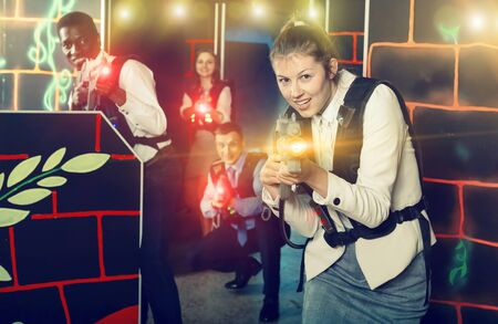Woman in a business suit holding her laser gun and playing laser tag with colleagues 写真素材