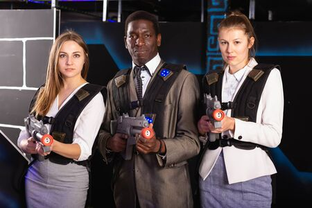 African man and two European women in business suits at laser tag room