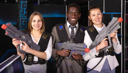 African male and two caucasian women holding laser guns and posing at laser tag room 写真素材