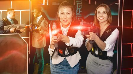 Portrait of two  positive women in business suits playing laser tag with co-workers