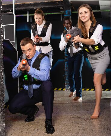 Group of satisfied  positive  smiling colleagues holding laser pistols playing laser tag game