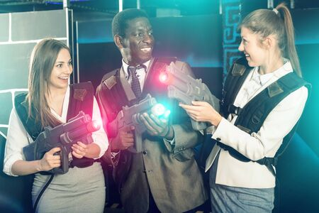 Smiling  positive glad associates – afro man and two European women posing at laser tag room
