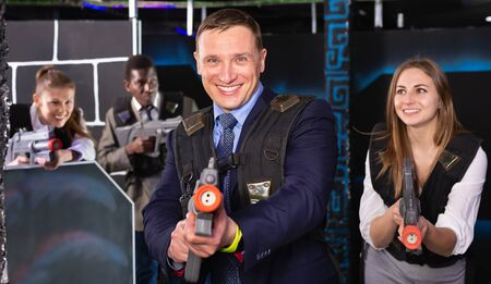 Man in the business suit holding a his laser gun and playing laser tag with colleagues