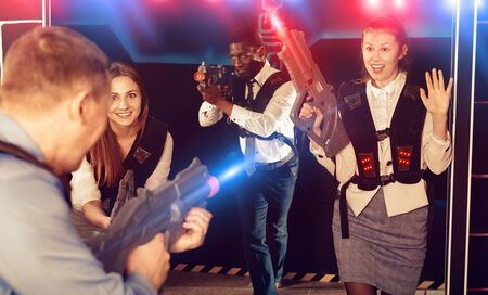 Glad positive  men and women in business suits playing laser tag emotionally in dark room