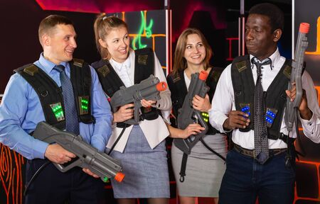 Group of glad co-workers holding laser guns and posing at laser tag room 写真素材