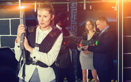Emotional portrait of young female playing laser tag with her co-workers in dark room