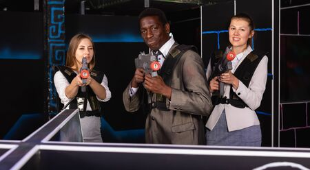 African male and two fine caucasian women holding laser guns and posing at laser tag room 写真素材