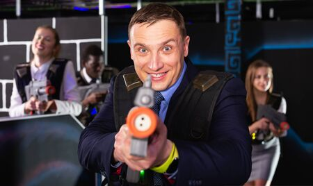 Emotional portrait of male businessman playing laser tag with his co-workers on dark labyrinth