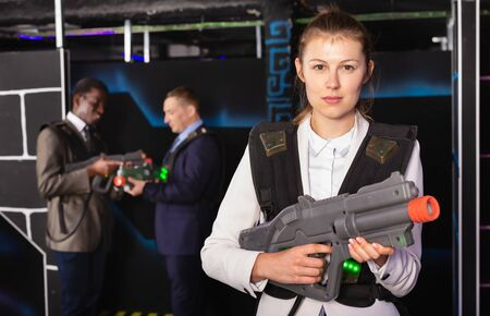 Woman in business suit holding laser gun and playing laser tag with colleagues 写真素材