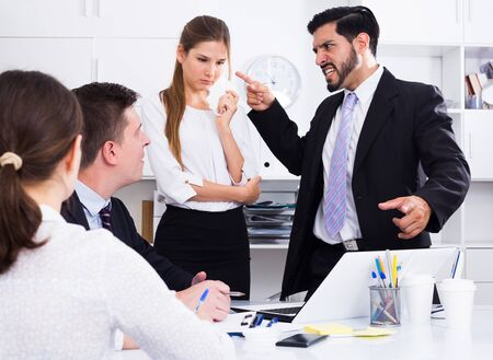 Businessman feeling angry to coworkers in office, pointing out mistakes in work