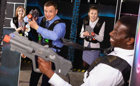 Group of satisfied smiling colleagues holding laser pistols playing laser tag game