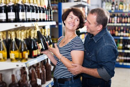 Husband and wife selecting a vine at the grocery store 写真素材 - 129843410