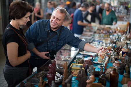 Elderly man and woman aged consider things in flea market