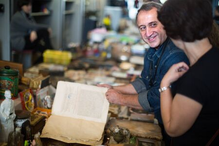 caucasians man and woman aged consider things in flea market