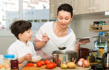 Happy family of young mother and preteen son cooking together at home 写真素材