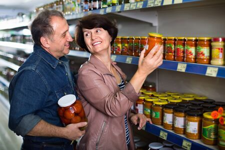 Cheerful husband and happy wife selecting a snacks at the grocery store