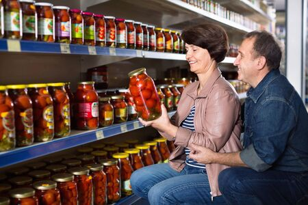 Husband and wife selecting a salted tomatoes at the grocery store