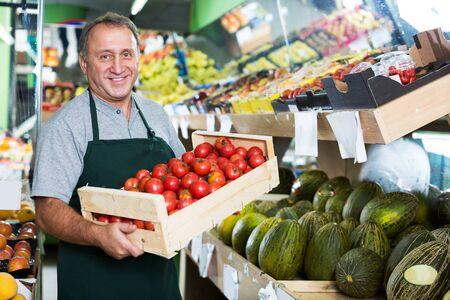 Vendedor macho maduro está demostrando tomates rojos frescos en la tienda