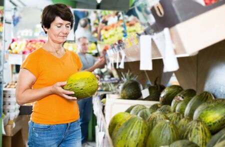 Smiling female is choosing green melon in the supermarket Фото со стока