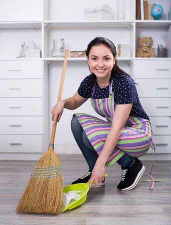 Young mistress sweeping floors in house with broom and shovel