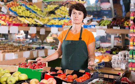Portrait of adult woman seller who is standing on her workplace in supermarket