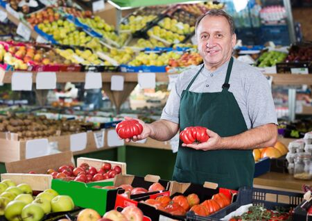 Positive man seller is standing with box with tomatos in the supermarket Фото со стока
