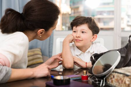 Dreamy preteen boy listening to mother who talking to him at home at table
