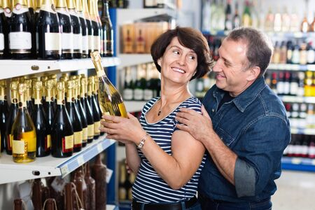 Portrait of an happy smiling elderly couple buying a wine at the grocery store 版權商用圖片