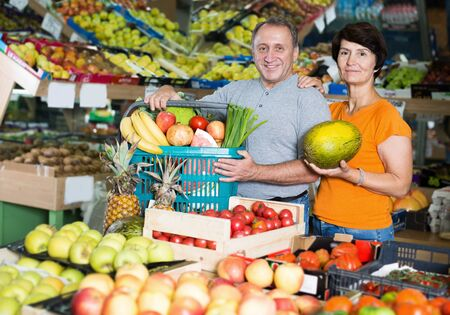 Family couple is standing with basket with vegetables and fruits in the hypermarket Фото со стока