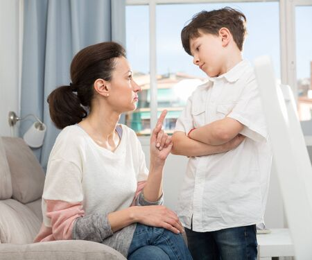 Preteen boy standing defiantly with arms crossed while his mother reprimanding him at home Stok Fotoğraf