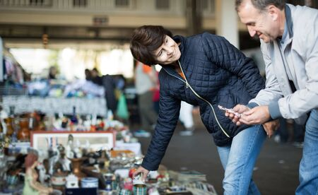 positive european adult man and woman are looking antiquariat at the market of old things 版權商用圖片