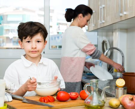 Positive preteen boy preparing food with his mother in cosy kitchen interior