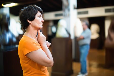 Thoughtful middle aged glad cheerful lady examining exposition in museum hall of ancient sculpture