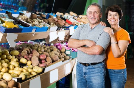 Portrait of positive couple who is standing in the fruit shop