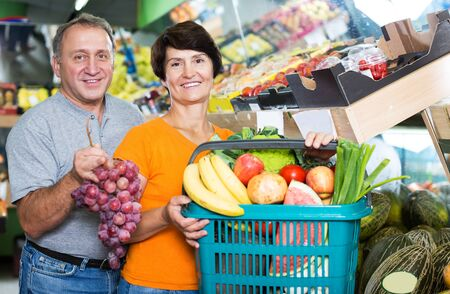 elderly male with female are standing with basket of purchases in the store.