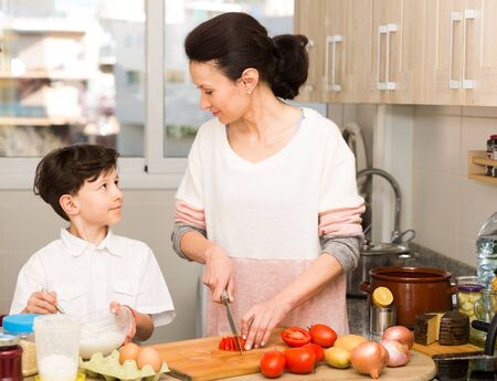 Positive woman and her preteen son preparing food and funny talking in cosy kitchen interior 写真素材