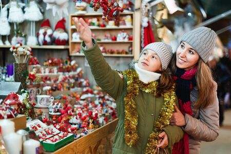 Positive female and her daughter are choosing decorations for Christmas tree in the market outdoor. Archivio Fotografico - 129806236
