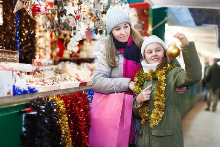 Smiling girl with woman are preparing for a Christmas and choosing the balls on tree outdoor. Focus on child Archivio Fotografico - 129806239