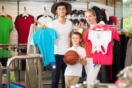 Mature positive parents with boy in school age shopping clothing in sport store