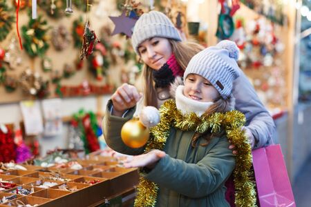 Smiling girl with woman are preparing for Christmas and choosing balls on a tree outdoor. Focus on child Archivio Fotografico - 129806275