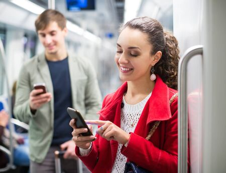 Passengers in metro wagon playing with smartphones